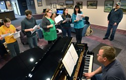 """Dusty Katzenberger, Kirk Gustafson, Jennifer Opdahl, Beth Legg and Connie Evans sing while Ben Bross adds piano music and director Torok Lewis watches practice. The Abuzz Theater Company will perform """"A Night of Musicals."""" - TRIBUNE/BARRY KOUGH"""