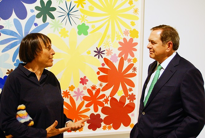 Standing in front of one of her brightly colored prints, artist Polly Apfelbaum talks with donor Jordan Schnitzer during the opening reception of an exhibit of her work in the museum of art bearing Mr. Schnitzer's name at Washington State University September 4. , - KAI EISELEIN
