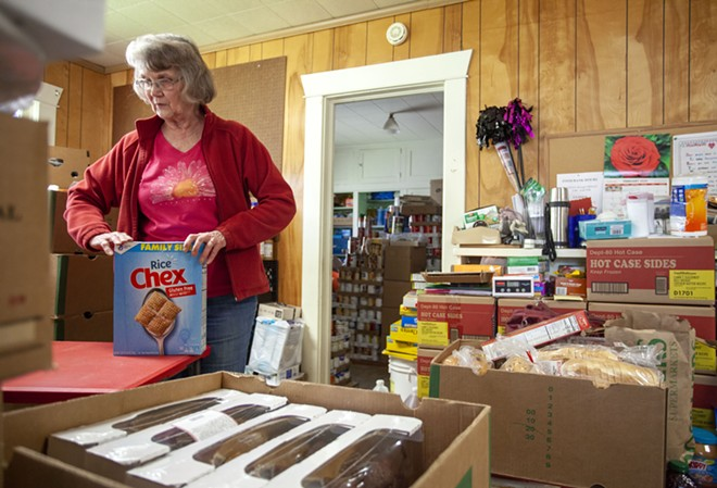 Director Linda Nickels organizes food on Tuesday before opening the Moscow Food Bank. Geoff Crimmins/Moscow-Pullman Daily News - GEOFF CRIMMINS/DAILY NEWS