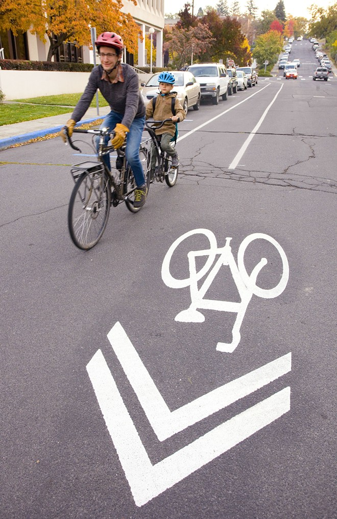Colin Priebe rides in a bicycle lane on East Fifth Street while taking his son, Colin Priebe, to school on Thursday in Moscow. - GEOFF CRIMMINS