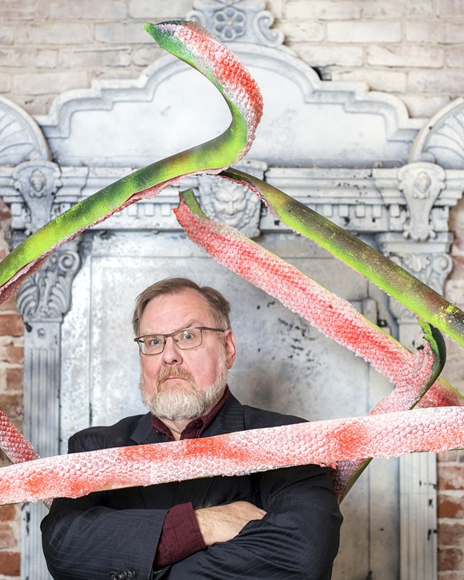 "Alien tentacles that will be used as props in the show, surround Patrick Broemeling, who is directing a radio show production of ""War of the Worlds"" for the Lewiston Civic Theater, as he poses for a portrait inside the Lewis and Clark State College Center for Arts and History on Friday evening. - TRIBUNE/PETE CASTER"