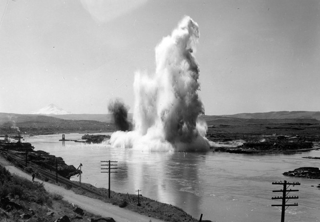 This photo was taken the first day of blasting in preparation for building The Dalles Dam. Blasting took place downstream from Celilo Falls which was inundated by water when the dam went into operation.