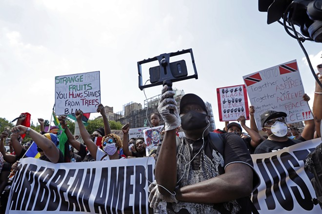 A man uses a bracket to hold his cell phone camera as he records speakers during a Caribbean-led Black Lives Matter rally at Brooklyn's Grand Army Plaza, Sunday, June 14, 2020, in New York. - AP PHOTO/KATHY WILLENS