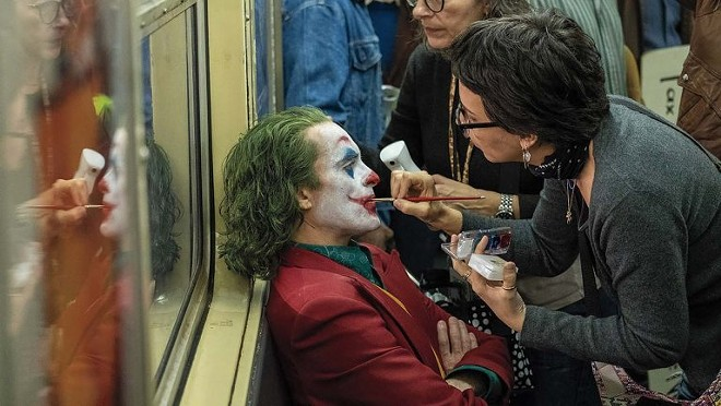 """Actor Joaquin Phoenix has makeup applied to his face on the set of """"Joker."""" On film sets, maintaining a 6-foot distance is not likely to happen as actors and crew members need to get close to each other. Photo credit: Warner Bros."""