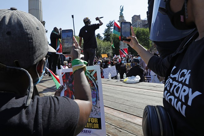 Two women use their cell phones to record a speaker during a Caribbean-led Black Lives Matter rally at Brooklyn's Grand Army Plaza, Sunday, June 14, 2020, in New York. A video of George Floyd's death went viral following the incident, capturing the world's attention. - AP PHOTO/KATHY WILLENS
