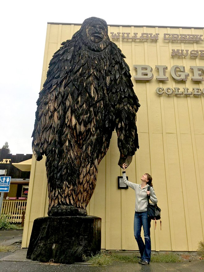 Laura Krantz holds hands with a 20-foot carved Big Foot in Willow Creek, Calif.