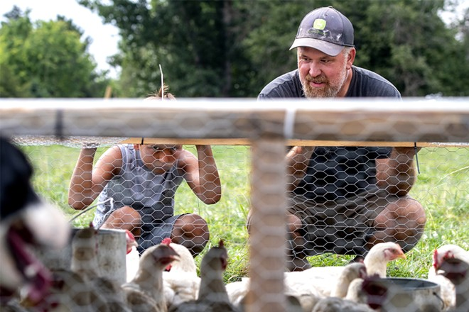 Wes Barnes and his son Jarrett Barnes, 8, look into their movable chicken coop as their herding dog Waitress (left) keeps a close eye on the chickens at the Barnes' home and farm property off Powers Avenue in Lewiston on Saturday. August Frank/Tribune - AUGUST FRANK/TRIBUNE