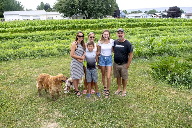 The Barnes family of Julie Barnes (from left), Jaylen Barnes, Jarrett Barnes, 8, Kadence Barnes, 15, and Wes Barnes, joined by dogs Rogue the golden retriever and Angus, stand in front of their fields of vegetables on Saturday. August Frank/Tribune - AUGUST FRANK/TRIBUNE