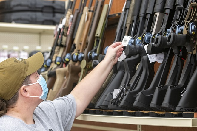 "Andrea Long, of Clarkston, examines firearms at Tri-State Outfitters in Moscow. In reference to the ongoing shortage of ammo and firearms, Long said, ""They just go off the shelf like crazy. I actually live in Clarkston and come up here just to see what they have."" - ZACH WILKINSON/FOR INLAND 360"