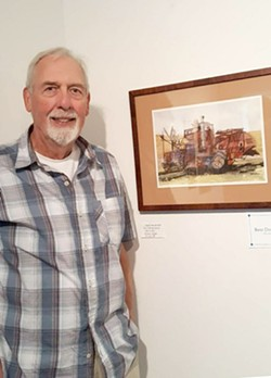 Artist Byron 'Barney' Saneholtz stands next to one of his works.