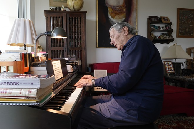 """Peter Fuchs plays the piano at his home in Aventura Fla., Tuesday, Feb. 23, 2021. Fuchs and his wife Veronica host a Facebook Live show called """"Stump the Maestro"""". At the start of the show Fuchs plays tunes that viewers try to guess. Then viewers request songs, mostly Broadway show tunes, '50s classics, movie soundtracks, jazz standards and some Beatles music, and Fuchs is a former Broadway composer, conductor and Holocaust survivor. - AP PHOTO/MARTA LAVANDIER"""