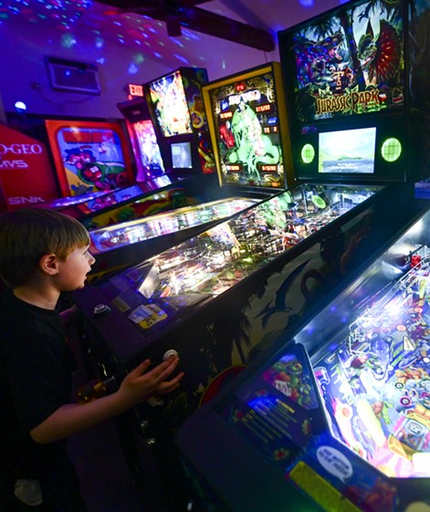 Patrick Martin, 6, plays a Jurassic Park pinball machine at Arcade1upClarkston on Friday afternoon in Clarkston. - PETE CASTER/360