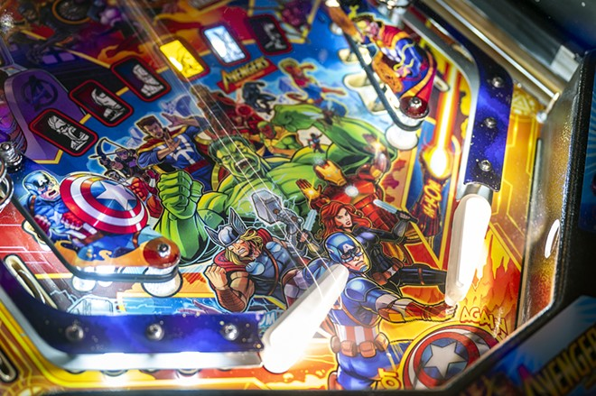 A pinball shoots off a paddle past the colorful background of the Avengers as Brian Boles of Lewiston plays pinball at Arcade1upclarkston on Friday afternoon. - PETE CASTER/360