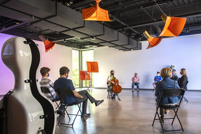 """An audience surrounds Ruth Boden as she plays the cello in the Jordan Schnitzer Museum of Art pavilion at Washington State - University. Boden's performance is in collaboration with Seattle-based artist, Trimpin's, interactive sound sculpture called """"Ambiente432,"""" which consists of 12 motion-responsive resonator horns. """"The purpose of the music was to recenter and open up our minds to the fact that there is still live art and live music,"""" Boden said. - ZACH WILKINSON/INLAND 360"""