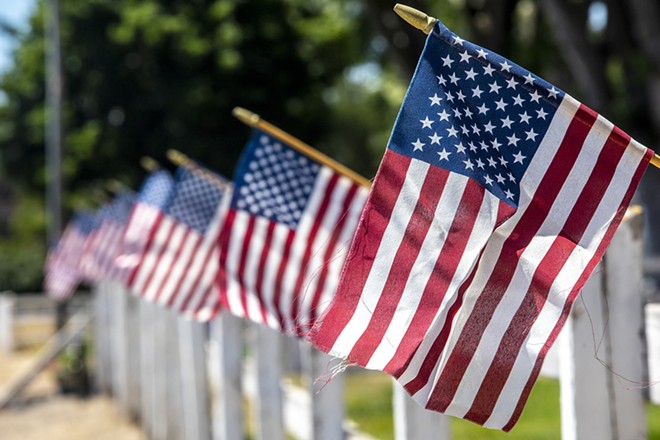 Flags fly along a fence line in Lewiston this week in anticipation of the July 4 holiday. - AUGUST FRANK