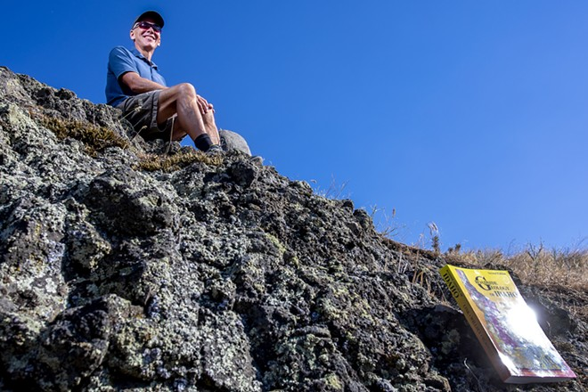"""Keegan Schmidt sits atop Columbia River basalts at the top of the Lewiston Grade on Thursday. Schmidt is one of the authors of the book """"Roadside Geology of Idaho."""" - AUGUST FRANK/360"""