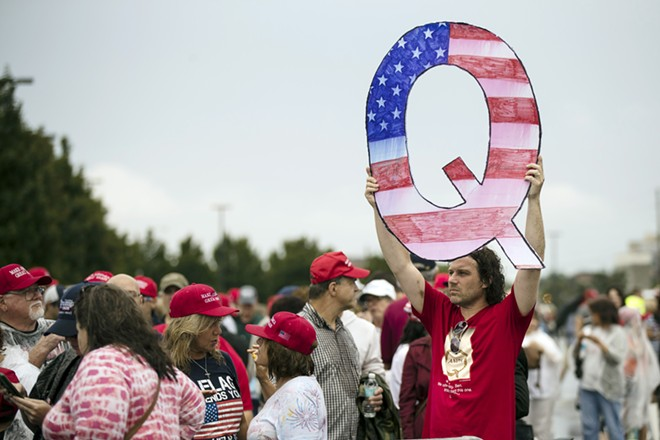 """In this Aug. 2, 2018, file photo, David Reinert holding a Q sign waits in line with others to enter a campaign rally with President Donald Trump in Wilkes-Barre, Pa. A far-right conspiracy theory formed online has crept into the mainstream political arena. It's called QAnon, and it centers on the baseless belief that President Donald Trump is waging a secret campaign against enemies in the """"deep state."""" - AP PHOTO/MATT ROURKE"""