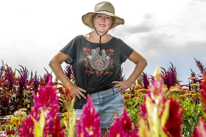 Taugher proudly stands among her flowers. - ZACH WILKINSON / INLAND 360