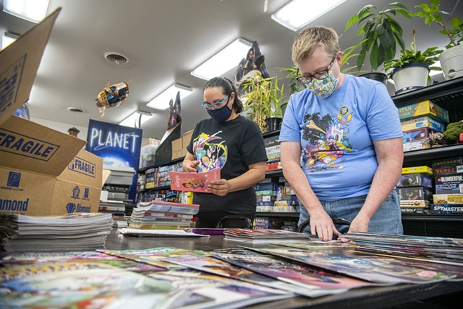 Angelita Slaysman, left, works with owner Katherine Sprague to sort through and label stacks of comic books that will be given away as part of Free Comic Book Day at Safari Pearl in Moscow. - ZACH WILKINSON/INLAND 360