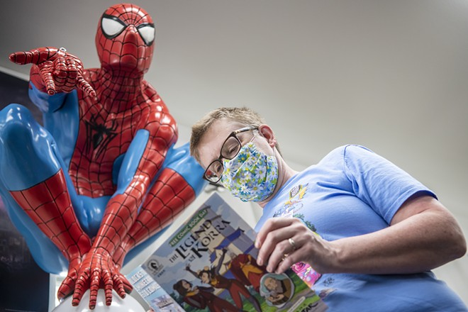 Safari Pearl owner Katherine Sprague flips through a comic book while standing underneath a statue of Spider-Man that is displayed in the front of the store. - ZACH WILKINSON/INLAND 360