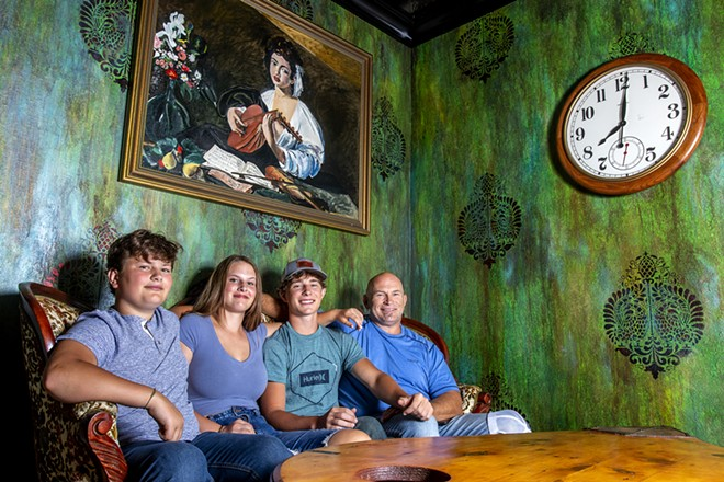 From left: Grant Stevens, 13, Caroline Stevens, 16, Jack Stevens, 17, and Geoff Stevens sit on a couch for a portrait at Mystic Cafe in Lewiston. - AUGUST FRANK/INLAND 360