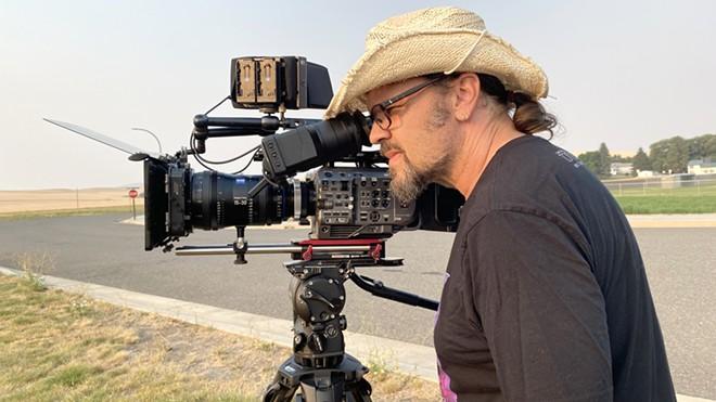 Director Rantz Hoseley looks through the eyepiece of a camera.
