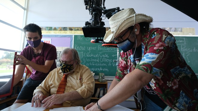 Director Rantz Hoseley discusses the action and camera angles with actor Patrick Broemeling while Vin Carlston, key grip, adjusts the glare coming off - the pages. - DAN BLAKNEY