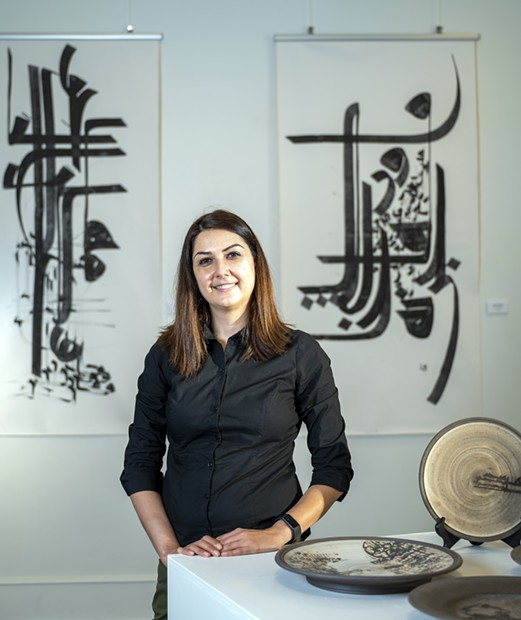 """Tirazheh Eslami — an artist, faculty art professor at Lewis-Clark State College and exhibit coordinator — poses for a portrait in behind Persian pottery on display at the Lewis-Clark State College Center for Arts & History in downtown Lewiston.  Eslami's show """"Persepolis: Introducing Persian Culture to the West"""" will open on Sept. 24. - PETE CASTER/360"""