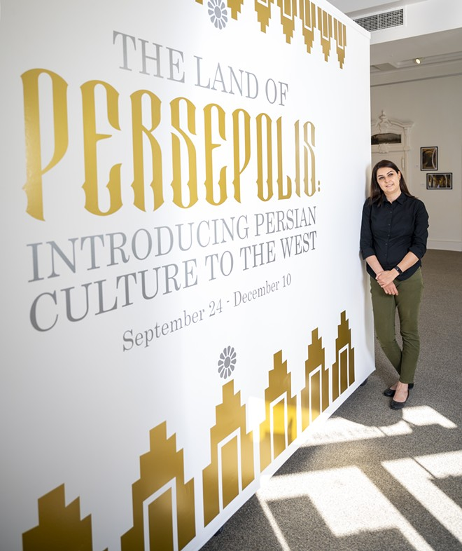 """Tirazheh Eslami — an artist, faculty art professor at Lewis-Clark State College and exhibit coordinator — poses for a portrait in front of the entrance of the """"Persepolis: Introducing Persian Culture to the West"""" sign on Thursday at the Lewis-Clark State College Center for Arts & History in downtown Lewiston. - PETE CASTER/360"""