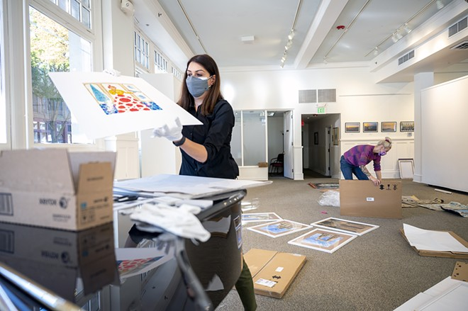 """Exhibit coordinator Tirazheh Eslami takes out a piece of art sent from Iran as she prepares to frame it with the help of intern Josephine Wimer (right) as they prepare for the opening of """"Persepolis: Introducing Persian Culture to the West"""" on Thursday at the Lewis-Clark State College Center for Arts & History in downtown Lewiston. - PETE CASTER/360"""