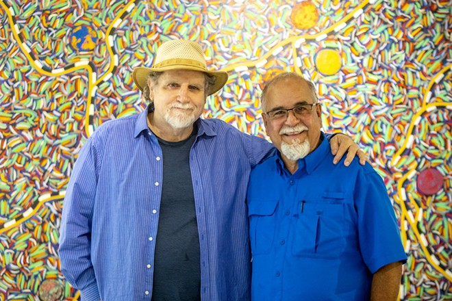 """Ray Esparsen and Sean Cassidy stand in front of one of Esparsen's paintings, titled """"Maps of Place and Meeting"""" at the Lewis-Clark State Center for Arts & History exhibit as part of the Beautiful Downtown Lewiston's annual Artwalk. - AUGUST FRANK/360"""
