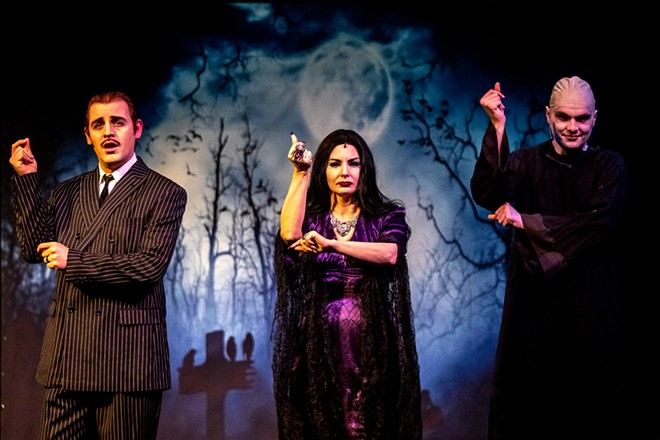 Micheal Keene, playing Gomez Addams, Amy Stout, playing Morticia Addams, and Aven Sparkman, playing Uncle Fester, snap their fingers during the opening song for the Addams Family at the old Lewiston High School on Monday evening. - AUGUST FRANK/360