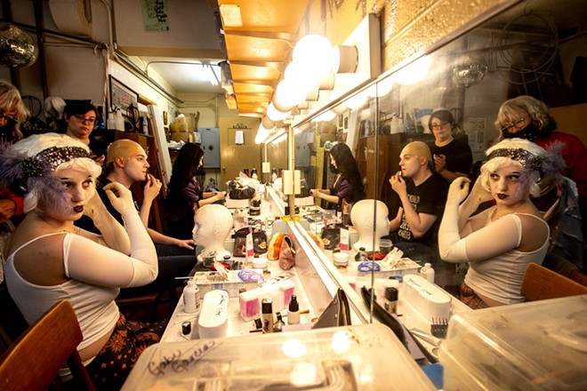 Elliss Dilling (left), playing a flapper ancestor, Aven Sparkman, playing Uncle Fester, and Amy Stout, playing Morticia Addams, prepare their makeup and costumes before a rehearsal for the Addams Family at the old Lewiston High School on Monday evening. - AUGUST FRANK/360
