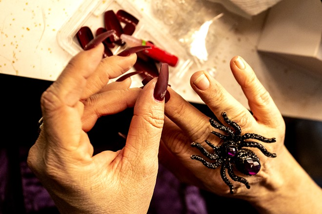 Amy Stout, playing Morticia Addams, puts long nails on before a rehearsal for the Addams Family at the old Lewiston High School on Monday evening. - AUGUST FRANK/360