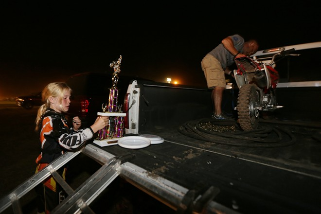 10 year old 70 cc little girl amateur rider Olivia Dixon, left, holds her 2nd place trophy as her father James loads her bike onto their truck after the 14th Annual Moto X. - YOUNG KWAK