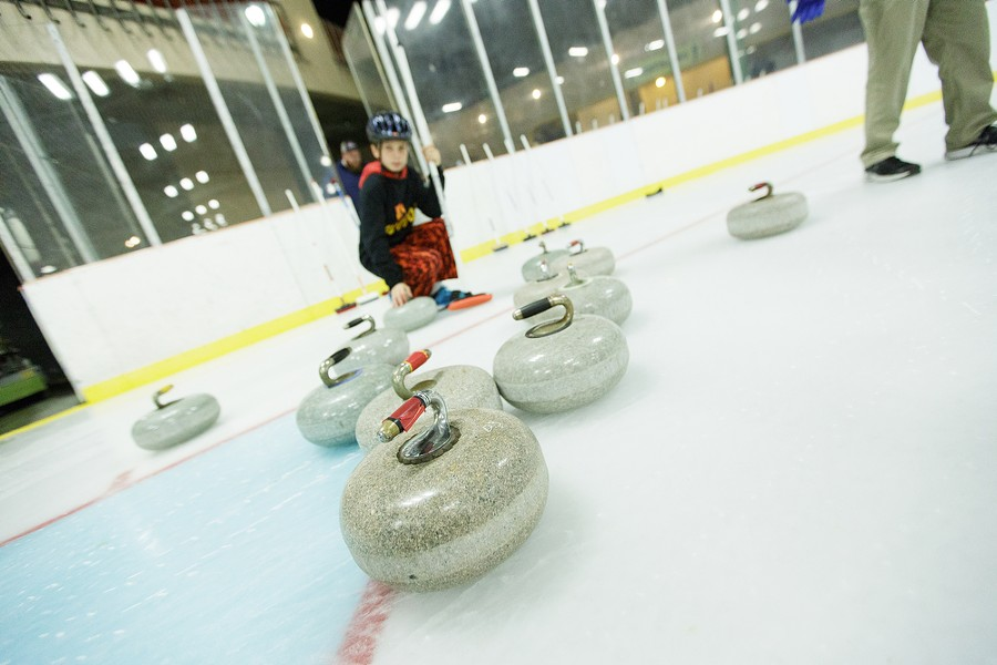 10-year-old Lilac City Curling Club member Ethan Thompson kneels next to some curling rocks. - YOUNG KWAK