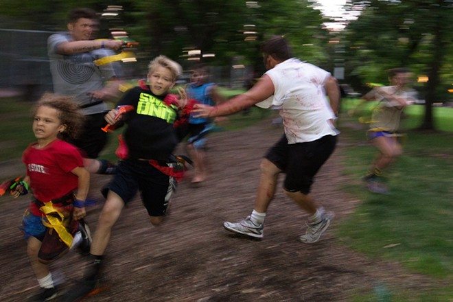 12-year-old race participant Avery Sundheim, center, avoids zombie Caleb Heath. - YOUNG KWAK