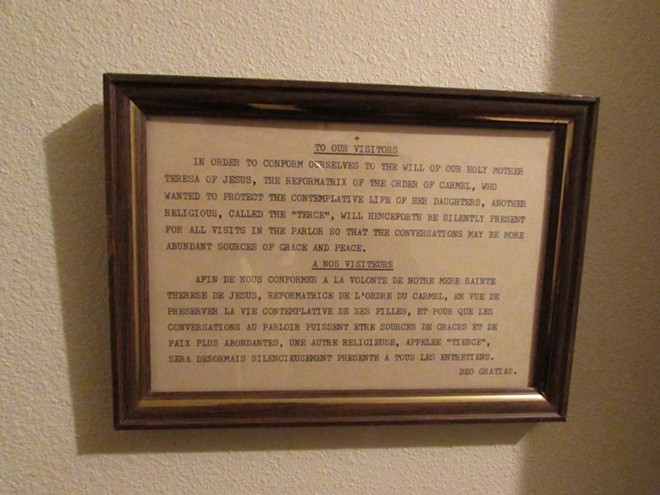 "A notice explaining, in English and French (with a Latin ""Thank You"") that another nun will be silently listening in to conversations held through the grate in the parlor. - DANIEL WALTERS"
