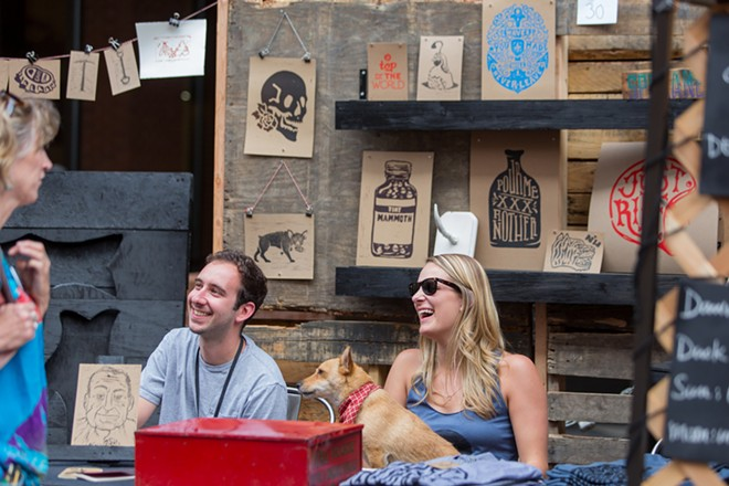 Aaron Abolofia of Tiny Mammoth Ink, left, sits with his friend Melissa Estma and dog Lola at his booth. - MATT WEIGAND