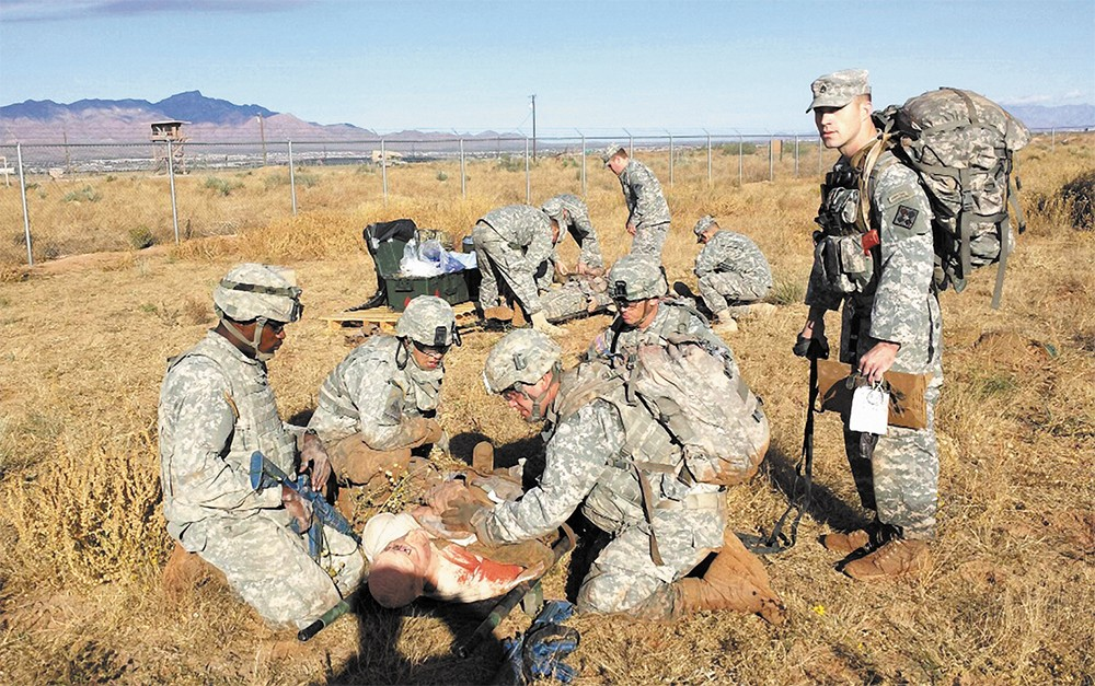 "Adam Sahlberg (above right) evaluates a team of medics as they evacuate and treat a mannequin with life-threatening injuries during a simulated ""care under fire"" scenario last November in the high desert outside Fort Bliss, near El Paso, Texas."
