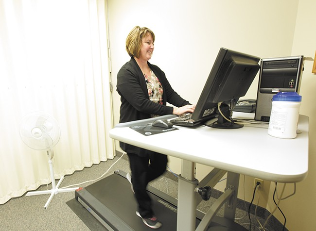 Administrative assistant Kris Stensatter strolls while she types at the Spokane Regional Health District's treadmill workstation. - YOUNG KWAK