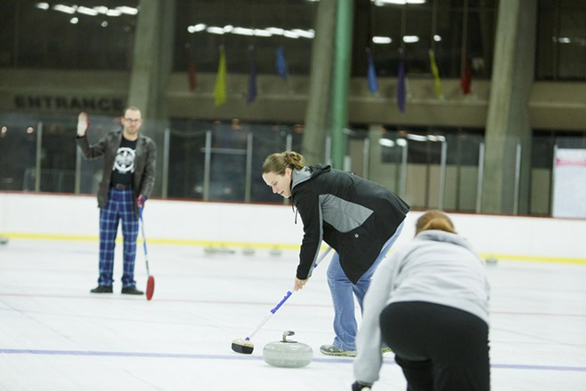 After student Lanelle Ramey, right, throws a rock, fellow student Christina Akinlosotu, center, sweeps as Lilac City Curling Club member Jon Escott looks on. - YOUNG KWAK