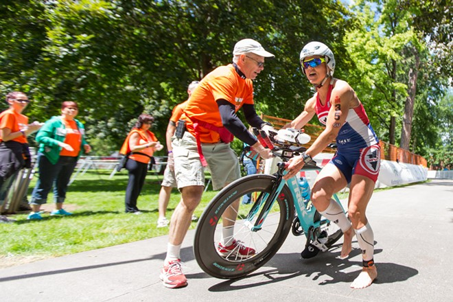 Ali Black, right, hands her bike to Brian Kingsburry. Black finished the race in 10:28:45 and in 97th place overall at the Coeur D'Alene Ironman. - MATT WEIGAND
