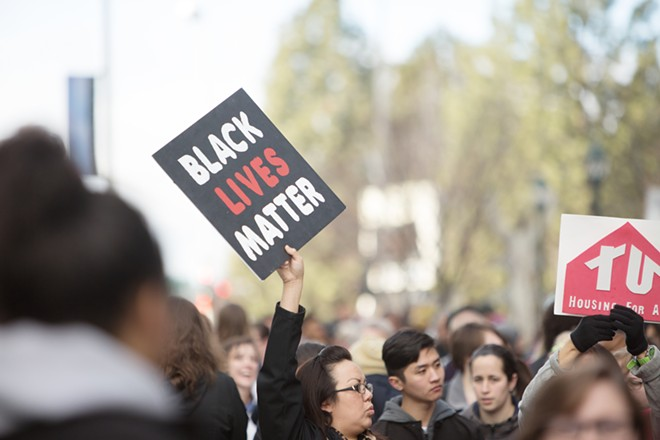 """Amber Abrahamsson, center, with a """"Black Lives Matter"""" sign. - YOUNG KWAK"""