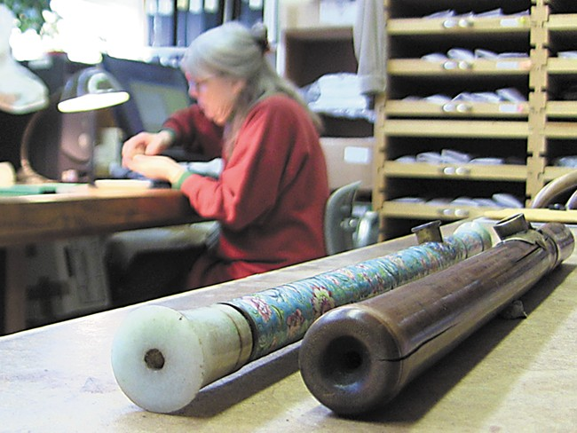 An enamel-decorated opium pipe, recently donated to the University of Idaho, rests next to one made of bamboo as Priscilla Wegars catalogs other opium artifacts. - ERIC FRANCAVILLA