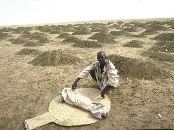 An Ethiopian refugee, in 1984, with a shrouded body of a child, a victim of hunger/drought, at a refugee camp in Sudan. - WILLIAM F. CAMPBELL/GETTY IMAGES