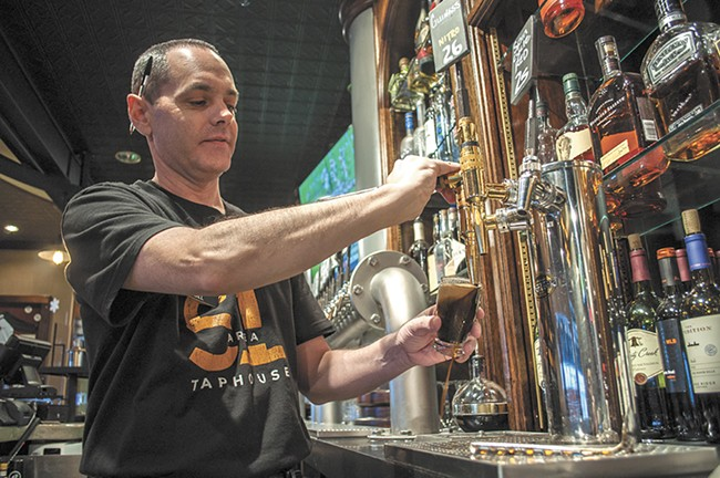 Area 51 Taphouse product manager Bill Matthew pours a stout from River City Brewing. - SARAH WURTZ
