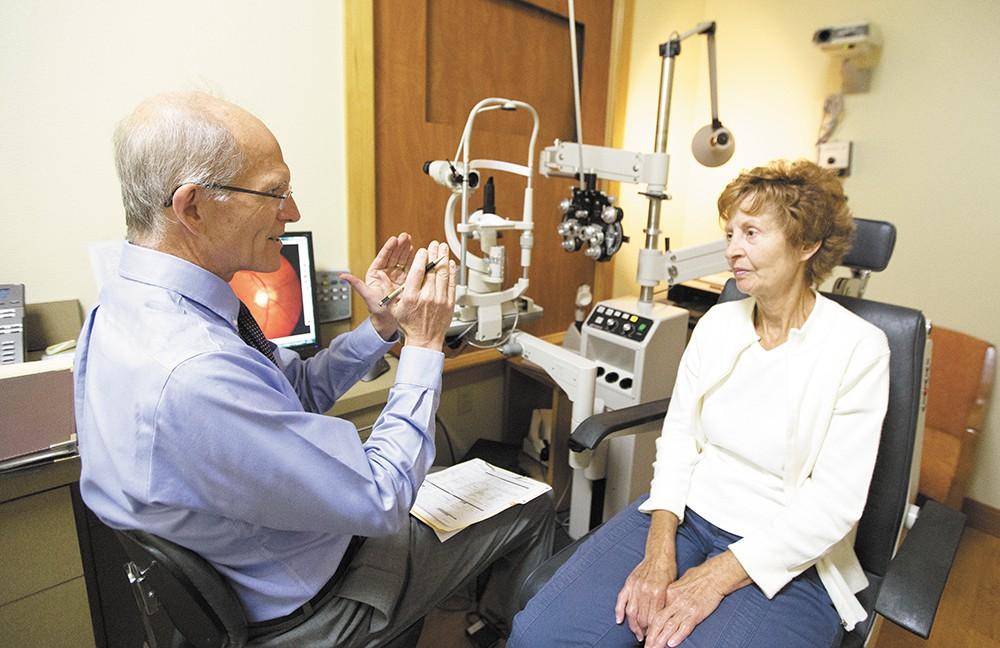 Arlene Bennett listens as Optometrist Todd Wylie explains the results of her eye exam. - YOUNG KWAK