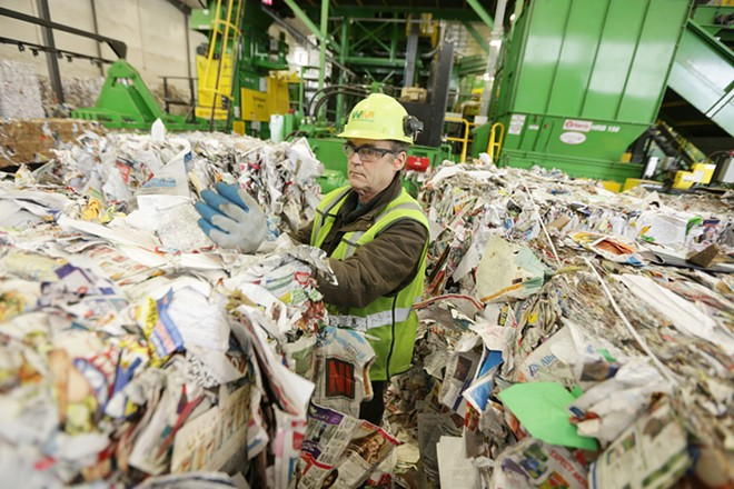 Rick McHenry removes items that don't belong from a bale of paper at Waste Management's SMaRT Center in Spokane on April 10. - YOUNG KWAK