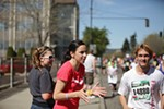 Barb Anderson, center, and her daughter Avi cheer runners on Broadway Avenue.